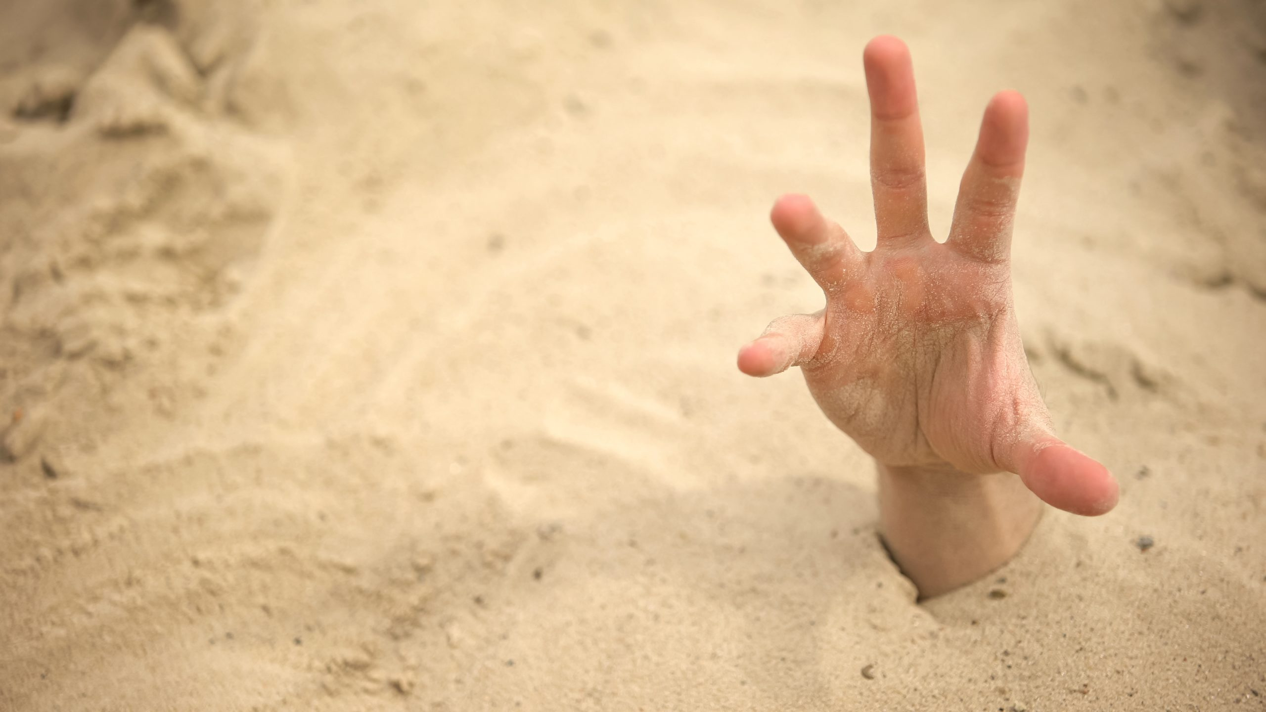 Une main qui sort du sable pour imager le piège