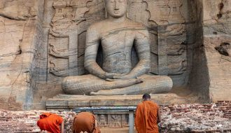 Moines priants devant une statut de Bouddha